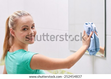 people, housework and housekeeping concept - happy woman cleaning mirror with rag at home - stock photo