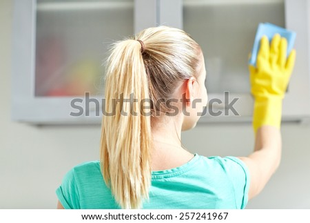 people, housework and housekeeping concept - happy woman in protective gloves cleaning cabinet with rag at home kitchen - stock photo