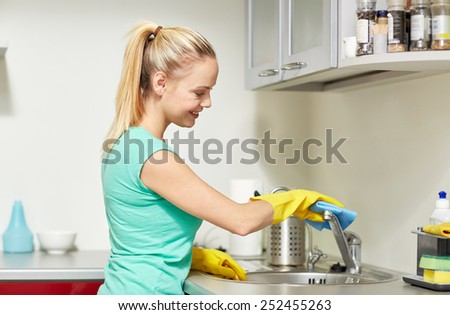 people, housework and housekeeping concept - happy woman in protective gloves cleaning tap with rag at home kitchen - stock photo