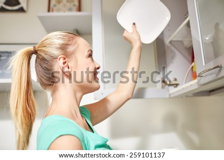 people, housework and housekeeping concept - happy woman putting plate to kitchen cabinet - stock photo
