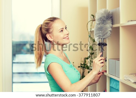 people, housework and housekeeping concept - happy woman with duster cleaning at home - stock photo