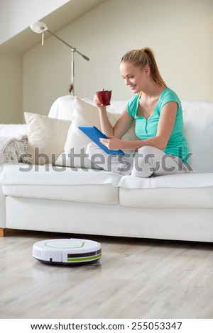 people, housework and technology concept - happy woman with tablet pc computer and robot vacuum cleaner drinking tea at home - stock photo