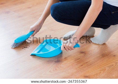 people, housework, cleaning and housekeeping concept - close up of woman with brush and dustpan sweeping floor at home - stock photo