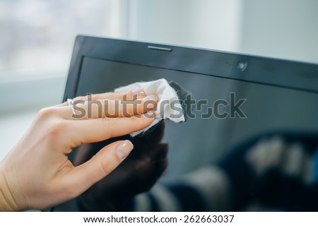 people, housework, electronics and housekeeping concept - close up of woman hand cleaning laptop computer screen with cloth - stock photo