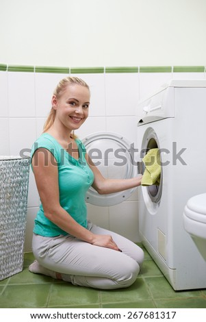 people, housework, laundry and housekeeping concept - happy woman putting laundry into washing machine at home - stock photo