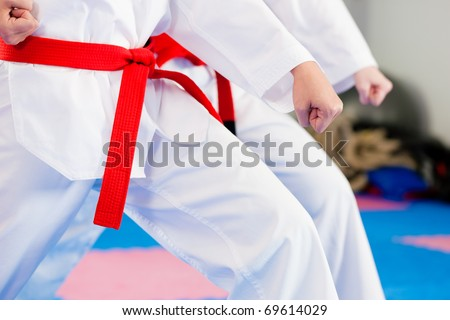 People in a gym in martial arts training exercising Taekwondo - stock photo