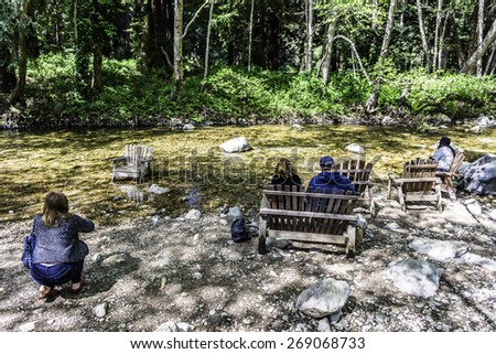 people in Adirondack chairs in the Big Sur river, near Carmel.  CA. on the California Central Coast.  - stock photo