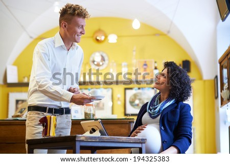 People in cafeteria, with barman serving espresso coffee to pregnant businesswoman sitting at table with tablet - stock photo