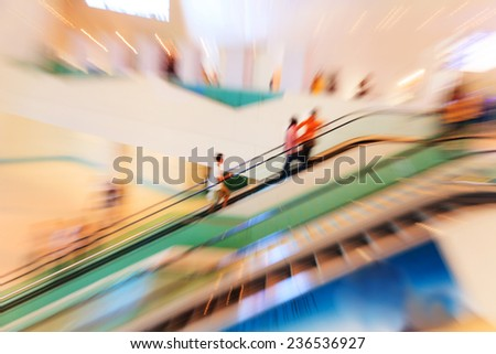 People in escalators at the modern shopping mall. motion blur - stock photo