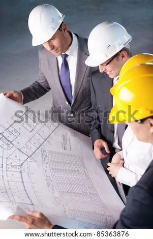 People in hard hats looking plan - stock photo