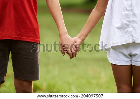People in love with little girl and boy holding hands in park. Cropped view - stock photo