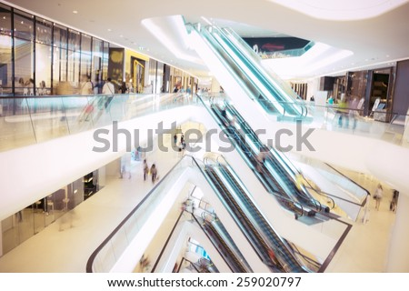 People in motion in escalators at the modern shopping mall.Defocused blur background. - stock photo