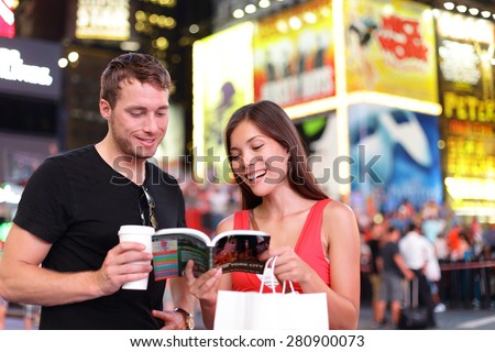 People in New York - happy couple on Times Square. Shopping young couple reading guidebook drinking coffee. Beautiful young couple having fun in city, Manhattan, USA. Asian woman, Caucasian man. - stock photo