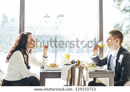 People in restaurant. Beautiful couple drinking wine. - stock photo