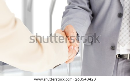 People in suit shaking hands against room with large window looking on city - stock photo