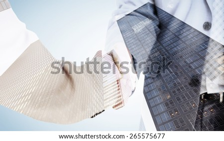 People in suit shaking hands against skyscraper - stock photo