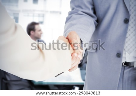 People in suit shaking hands against thoughtful businesswoman talking to her team during a meeting - stock photo