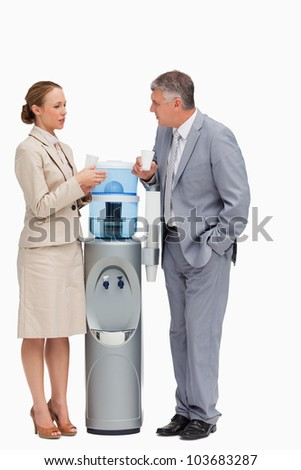 People in suit talking next to the water dispenser against white background - stock photo