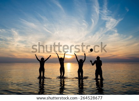 people in the sea at sunset play ball - stock photo