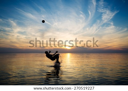 people in the sea at sunset plays with a ball - stock photo