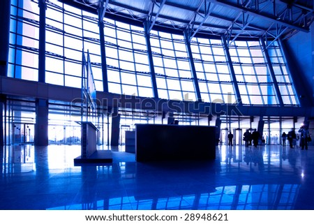 People in wide blue hall window in exposition center,righ copmosition - stock photo