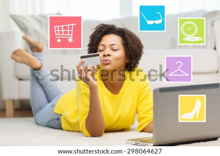 people, internet bank, online shopping, technology and e-money concept - happy african american young woman lying on floor with laptop computer and credit card at home over internet icons - stock photo