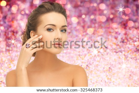 people, jewelry, holidays, luxury and glamour concept - woman wearing diamond ring over pink lights background - stock photo