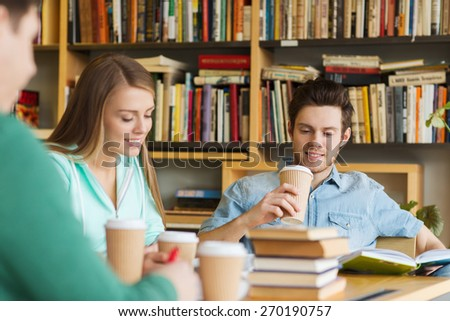 people, knowledge, education and school concept - group of happy students reading books, drinking coffee and preparing to exam in library - stock photo
