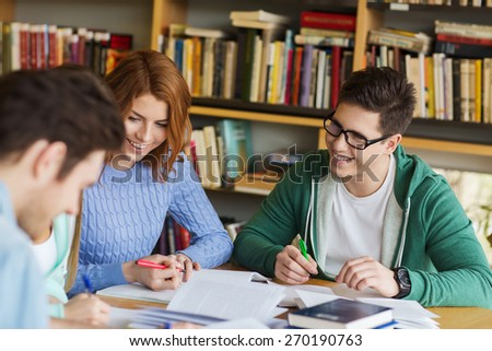 people, knowledge, education and school concept - group of happy students with books preparing to exam and writing in library - stock photo