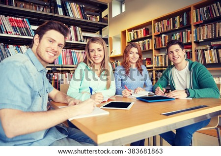 people, knowledge, education and school concept - group of happy students with tablet pc computers writing to notebooks in library - stock photo