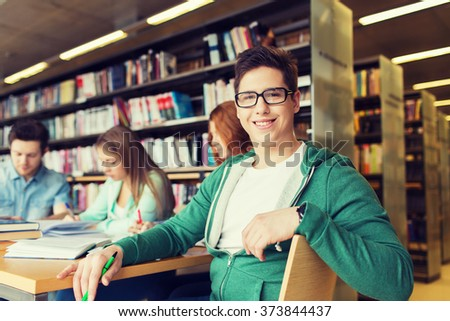 people, knowledge, education and school concept - happy student boy reading books in library - stock photo