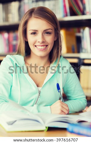people, knowledge, education and school concept - happy student gir with book and pen writing in library - stock photo