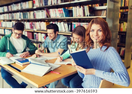 people, knowledge, education, literature and school concept - happy students reading books and preparing to exams in library - stock photo