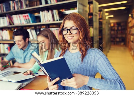 people, knowledge, education, literature and school concept - happy young woman in eyeglasses reading book and preparing to exams over group of students in library - stock photo