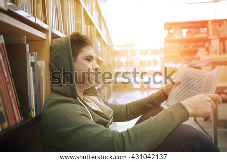 people, knowledge, education, literature and school concept - student boy or young man sitting on floor reading book in library - stock photo