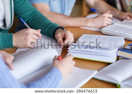 people, learning, education and school concept - close up of students hands with books or textbooks writing to notebooks - stock photo