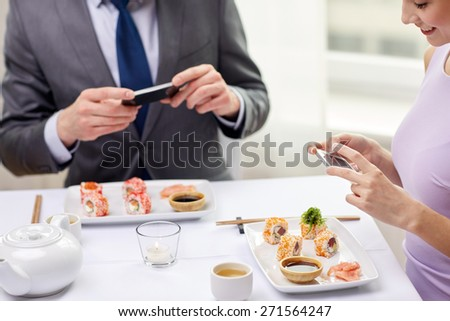 people, leisure, eating, food and technology concept - close up of couple with smartphones taking picture of sushi at restaurant - stock photo