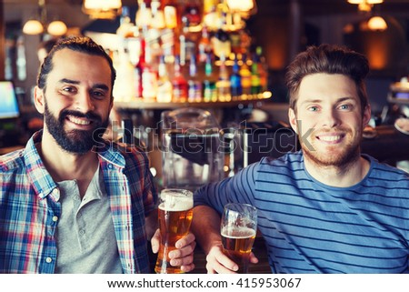 people, leisure, friendship and bachelor party concept - happy male friends drinking beer and talking at bar or pub - stock photo