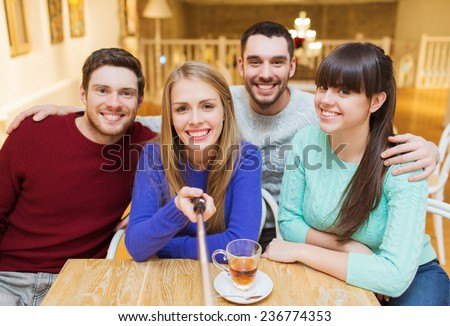 people, leisure, friendship and technology concept - group of happy friends with selfie stick taking picture and drinking tea at cafe - stock photo