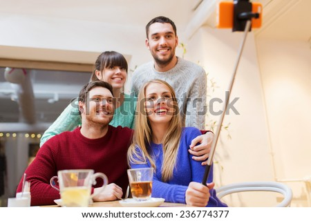 people, leisure, friendship and technology concept - group of happy friends with smartphone selfie stick taking picture and drinking tea at cafe - stock photo