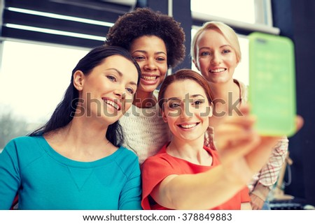 people, leisure, friendship and technology concept - happy young women taking selfie with smartphone - stock photo