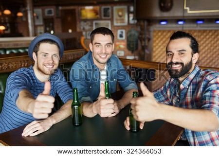 people, leisure, friendship, gesture and bachelor party concept - happy male friends drinking bottled beer and showing thumbs up at bar or pub - stock photo