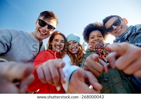 people, leisure, gesture and teenage concept - group of happy teenage friends pointing fingers on city street - stock photo