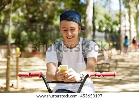 People, lifestyle and communication concept. Portrait of happy handsome teenage boy wearing cap backwards, using mobile phone while riding a BMX bike, smiling, messaging friends via social networks - stock photo