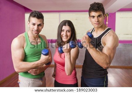 People lifting dumbbells weights posing in gym - stock photo