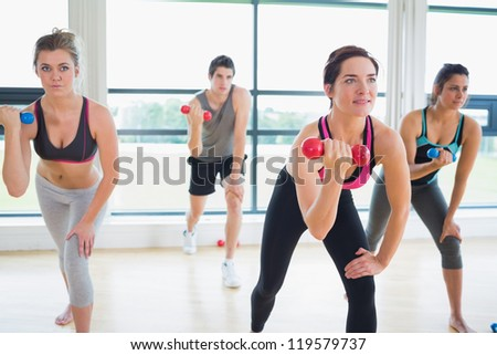 People lifting weights in aerobics class in fitness studio - stock photo