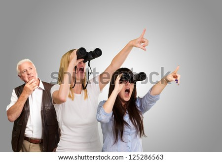 people looking through binoculars against a grey background - stock photo
