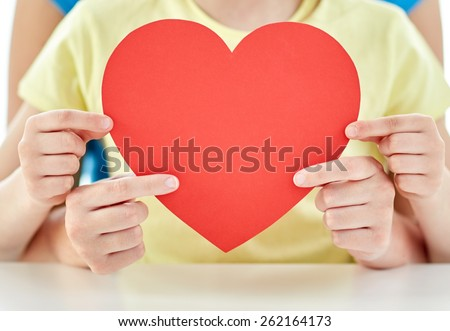 people, love, charity and family concept - close up of happy girl and mother holding red heart shape at home - stock photo
