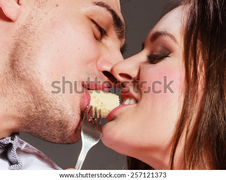 People love dating and happiness concept. Attractive couple eating banana together, man and woman sharing fruit face to face. - stock photo