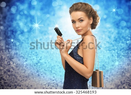 people, luxury, holidays and finance concept - beautiful woman in evening dress with vip card and handbag over blue lights background - stock photo